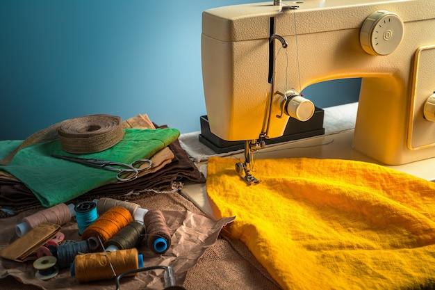 Красочный швейный фон с швейной машиной и аксессуарами на синем фоне.