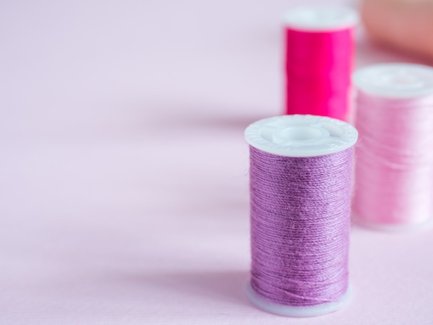 Colorful sewing buttons and thread on a pink background