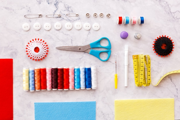 Colorful sewing and tailoring tools and items on light surface