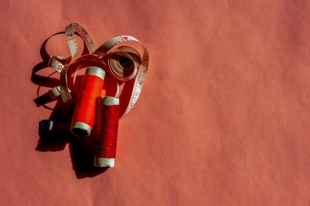 Красочные швейные нитки и рулетка на розовом фоне