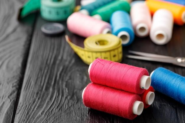 Красочные швейные принадлежности на черной деревянной поверхности