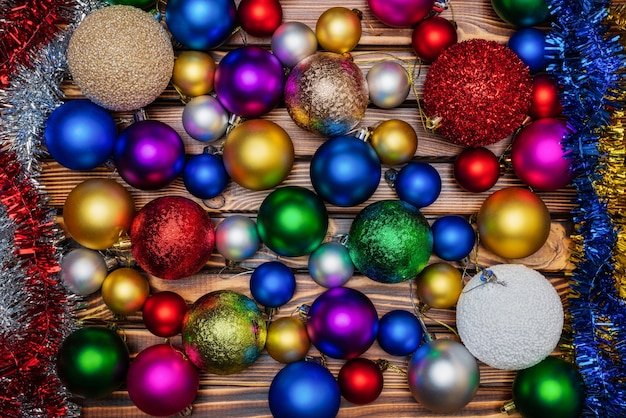 Colorful shiny christmas balls and tinsel on wooden table background. close-up view of xmas holiday decoration. beautiful still-life of flat lay festive composition for happy new year.