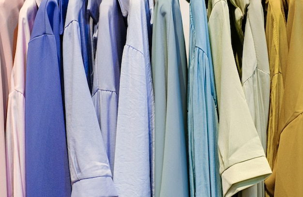 Colorful shirts on the hangers in the store close up