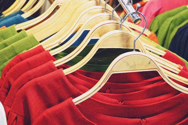 Colorful shirts hanging on rack close up