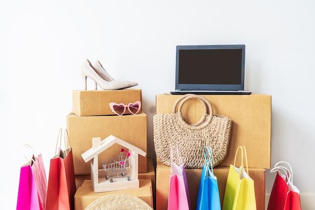 自宅で段ボール箱やファッションアイテムのスタックとカラフルなショッピングバッグ、コピースペースとウェブサイトのオンラインショッピングのコンセプト