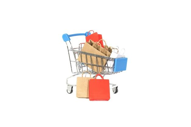 白で隔離されるカートでカラフルなショッピングバッグ。