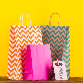 Colorful shopping bags with design on wooden table against yellow background