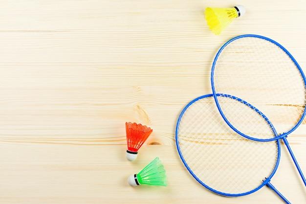 カラフルなシャトルコックとバドミントンラケットが木製の机の上に平らに置かれていました。スポーツとレクリエーションの概念