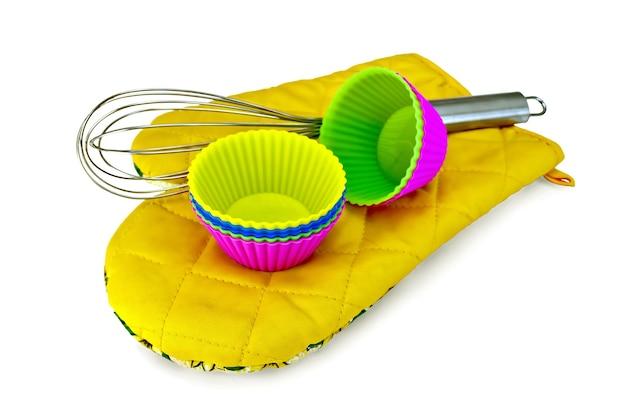 Красочные силиконовые формы для тортов, миксер на желтой тканевой прихватке, изолированной на белом