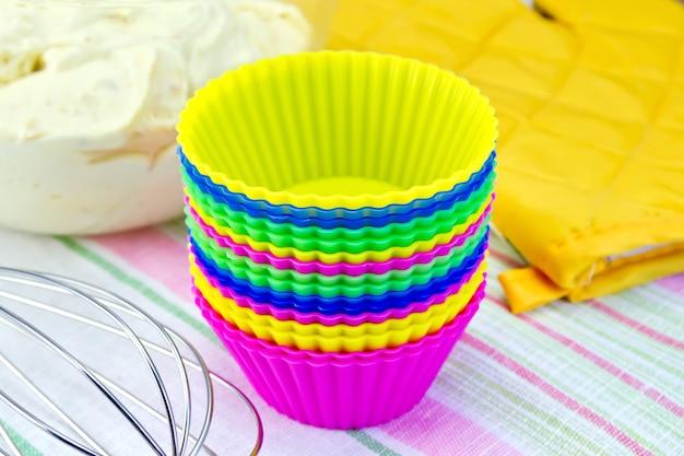 컵케이크, 믹서, 노란색 천 냄비 홀더, 린넨 배경의 유리 그릇에 든 반죽을 위한 다채로운 실리콘 몰드