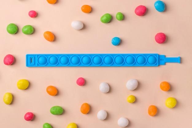 カラフルなシリコンおもちゃの抗ストレスポップイットブレスレット、色とりどりのキャンディーを背景に