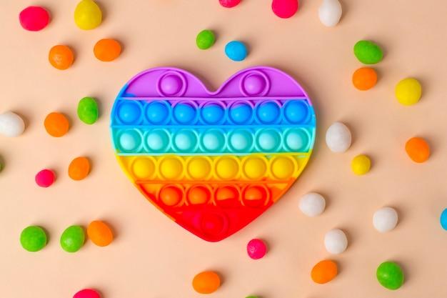 カラフルなシリコンおもちゃの抗ストレスポップイットブレスレット、ベージュの背景に色とりどりのキャンディー