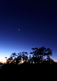 カラフルな空と夕暮れの森の家
