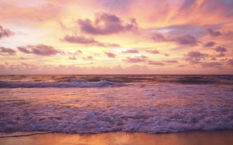 Colorful sky as a background. Soft wave of the sea on the sandy beach