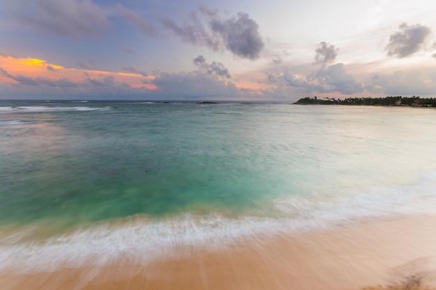Красочное небо на закате на пустынном тропическом пляже