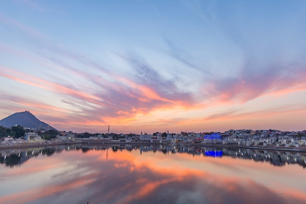 Colorful sky and clouds over pushkar, rajasthan, india. temples, buildings and colors reflecting on the holy water of the lake at sunset.