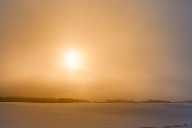 Красочное небо во время заката или восхода солнца в зимний сезон, заснеженное поле и туман