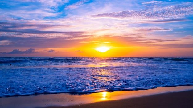 다채로운 하늘 일몰 또는 일출 다채로운 하늘 레코딩 및 모래 해안에 부서 지는 빛나는 파도 바다 표면에 아름 다운 빛 반사 놀라운 풍경 또는 바다 자연 배경입니다.