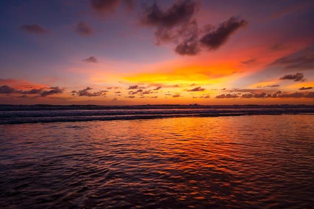 다채로운 하늘 일몰 또는 일출 다채로운 하늘 레코딩 및 모래 해안에 충돌 하는 빛나는 파도 바다 표면에 아름 다운 빛 반사 놀라운 풍경 또는 바다 자연 황혼 배경입니다.
