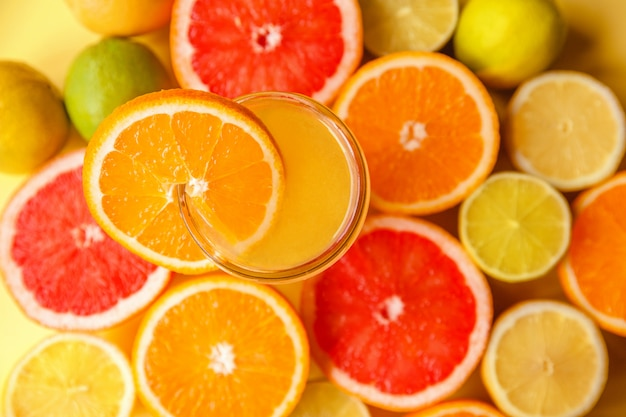 Colorful sliced citrus fruits close-up around a glass of orange juice and a slice of orange.