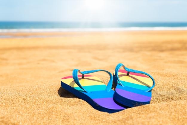 夏の日のビーチでカラフルなスリッパゲイプライドフラグビーチサンダル