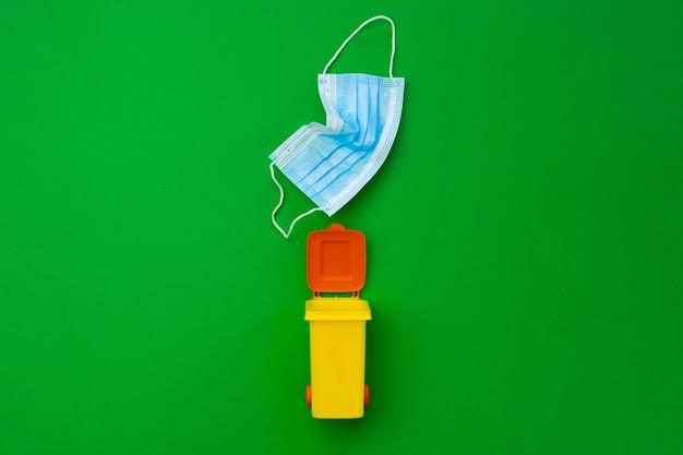 カラフルな小さなゴミは感染性マスクを使用しています、クローズアップ