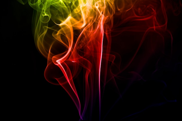 Colorful smoke over black background for overlay design