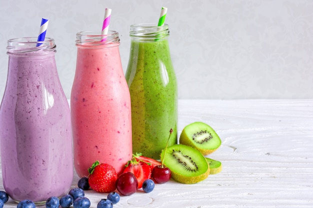 Colorful smoothie drinks in bottles with fresh fruits and berries