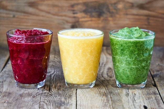 Colorful smoothies with beet, cucumber and orange on a wooden table