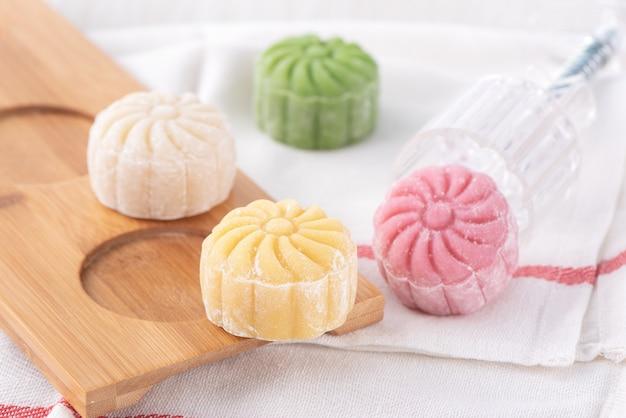 カラフルなスノースキン月餅、甘い雪の月餅、明るい木製の背景、クローズアップ、ライフスタイルの中秋節の伝統的なおいしいデザート。