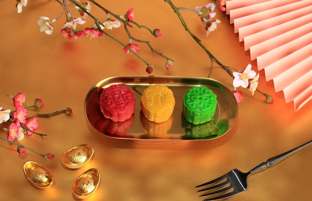 Colorful snow skin moon cake, sweet snowy mooncake, traditional savory dessert for mid-autumn festival on golden background, close up, lifestyle.