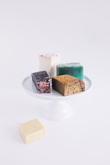 Colorful soap bars on cake stand over white background