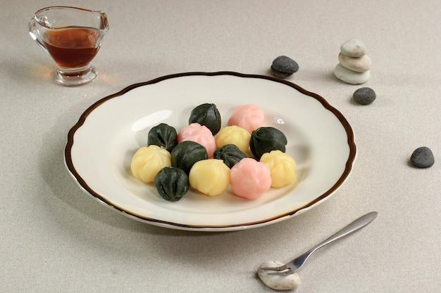 木製の皿にカラフルなソンピョンクルトオク(蜂蜜入り餅)。ソンピョンは元日または韓国の感謝祭の日に食べられる韓国の伝統的な食べ物です。