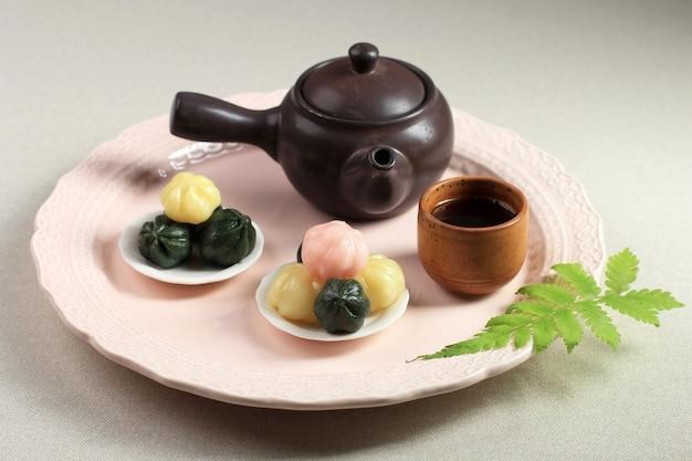 Красочный songpyeon kkultteok (рисовый пирог с медовой начинкой) в деревянной тарелке. сонпхён - это традиционная корейская еда, которую едят в новый год или в день корейской благодарности.