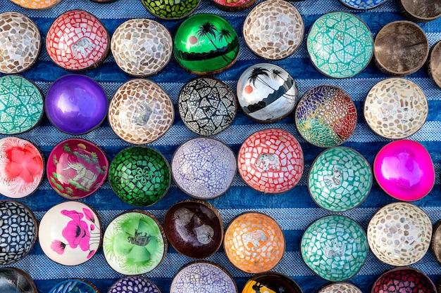 태국의 거리 시장에서 관광객들을 위한 다채로운 기념품 그릇. 코코넛 껍질로 만든 그릇, 클로즈업, 평면도