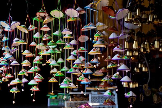 Красочные сувениры с колокольчиками висят на фасаде магазина в старом городе хойана. вьетнам