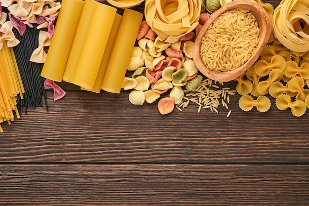 カラフルなスパゲッティ、タリアテッレ、ファルファッレ、ペンネ、ptititm、ヌードル、フジッリ、古い木製の背景にカネロニ