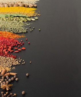 Colorful spices on black surface