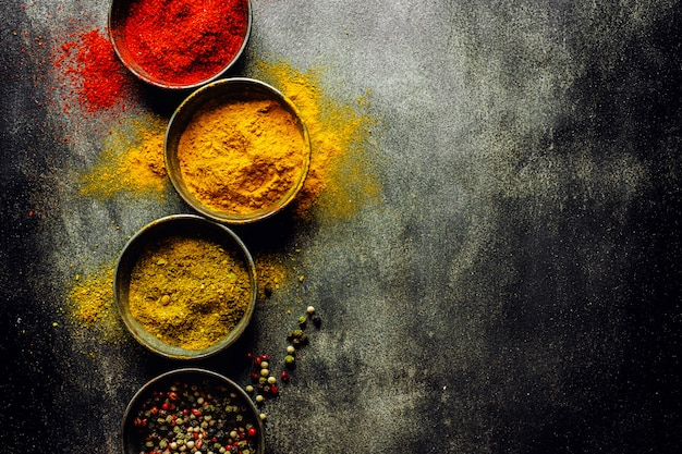 Colorful spices on dark surface
