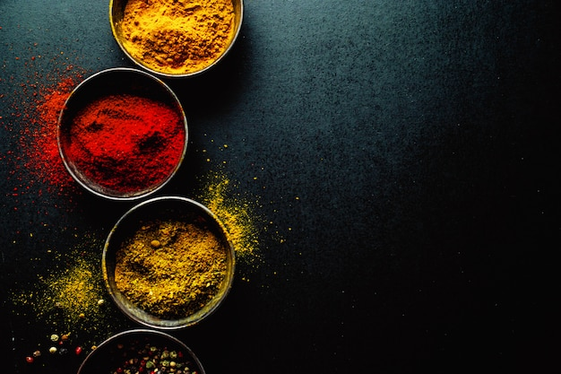 Colorful spices on dark table, copyspace