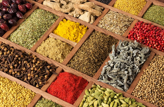Colorful spices and herbs in wooden trays.