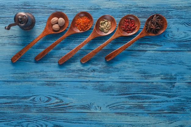 Colorful spices on wooden spoons