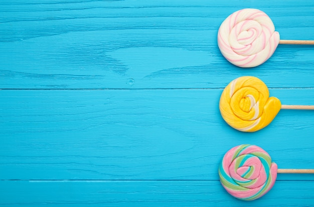 Colorful spiral lollipops on blue wooden table