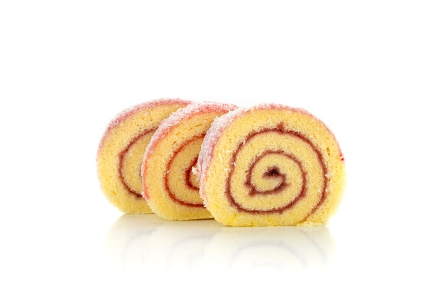Colorful sponge roll cake with raspberry jam and coconut flakes