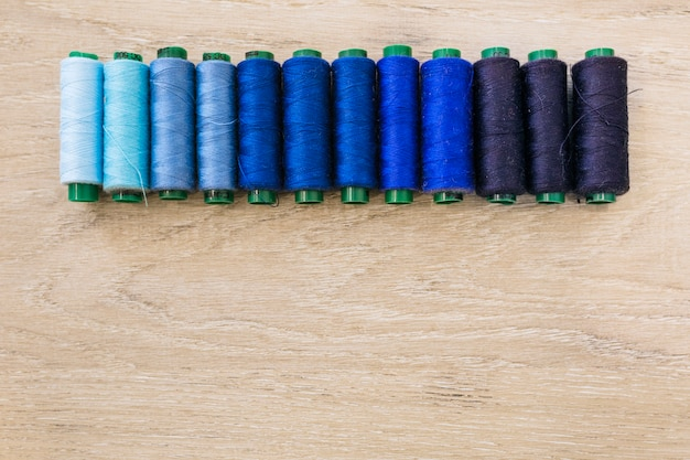 Colorful spool of threads on wooden backdrop