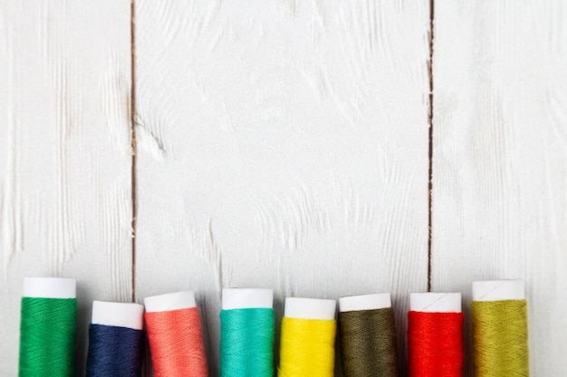 Colorful spools of threads on white wooden background with copy space