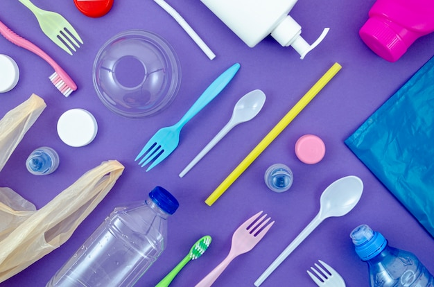 Colorful spoons and bottles on purple background