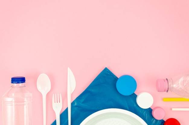 Colorful spoons and dish on pink background