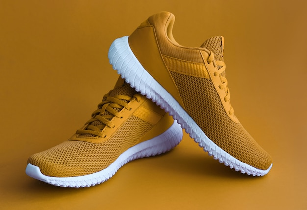 Colorful sport shoes on mustard color backround