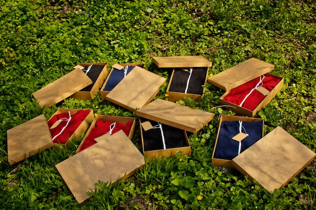 Colorful sportswear with tags folded in cardboard boxes lie on the ground with grass.